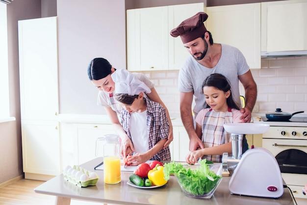 Família está de pé na cozinha e cozinhar. cara ajuda a garota a cortar pepino. Foto Premium