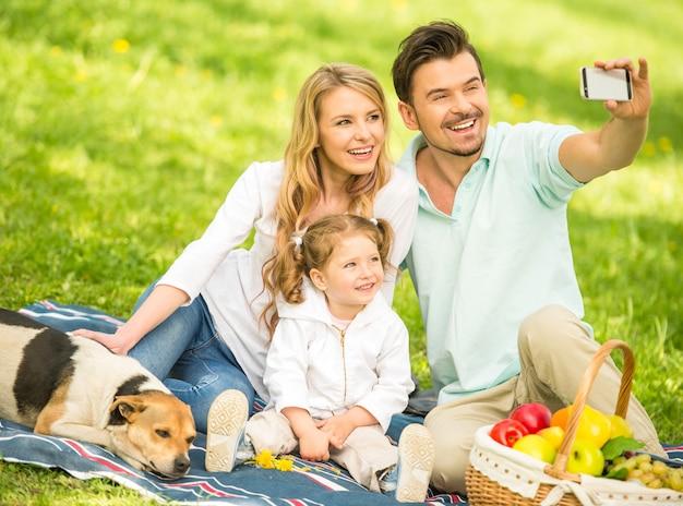 Família fazendo piquenique ao ar livre e fazendo selfie. Foto Premium