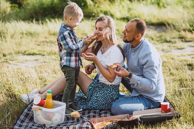 Família fazendo piquenique e comendo pizza no parque Foto gratuita