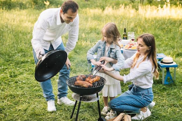 Família fazendo um churrasco na natureza Foto gratuita