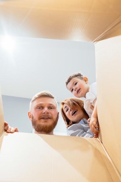 Família feliz acaba de se mudar para casa nova e olhar para a caixa Foto gratuita