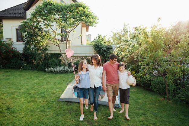 Família feliz andando na grama em frente a tenda ao ar livre Foto gratuita