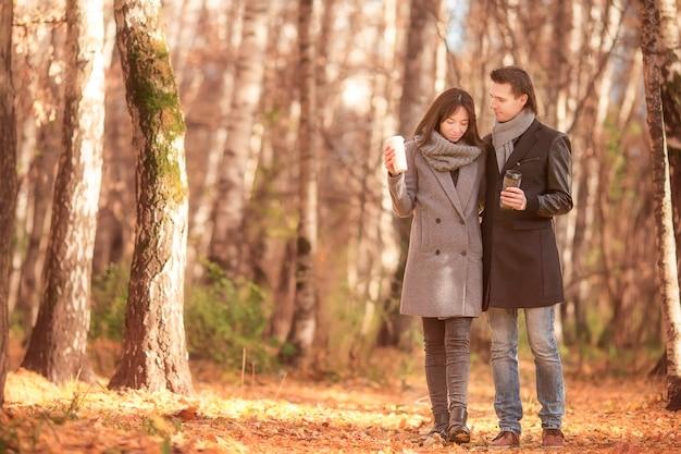 Família feliz andando no parque outono em dia ensolarado de outono Foto Premium