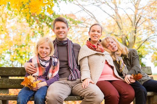 Família feliz, ao ar livre, sentar-se banco, em, outono Foto Premium