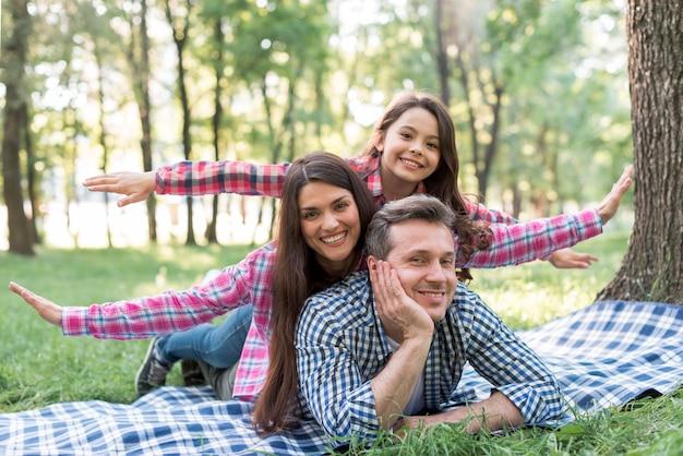 Família feliz, aproveitando o dia no parque Foto gratuita