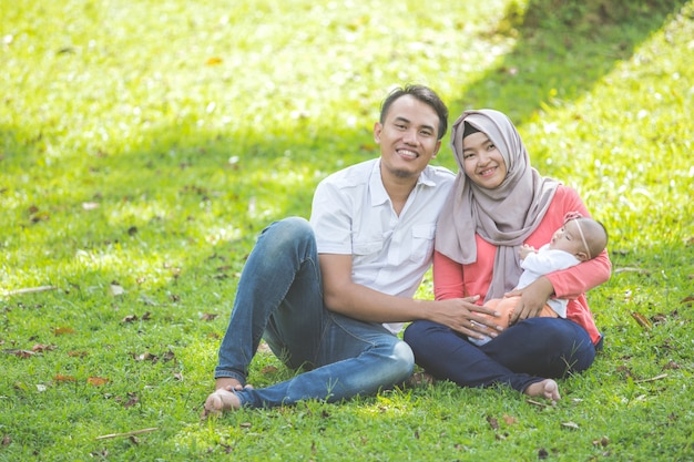 Família feliz asiática com bebê recém-nascido no parque Foto Premium