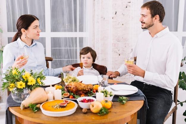 Família feliz bebendo na mesa festiva Foto gratuita