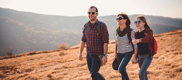 Família feliz, caminhadas juntos em uma montanha Foto Premium