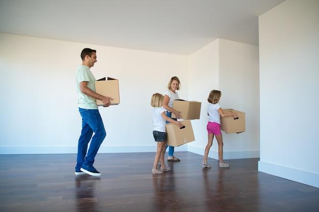 Família feliz carregando caixas de papelão do quarto vazio Foto gratuita