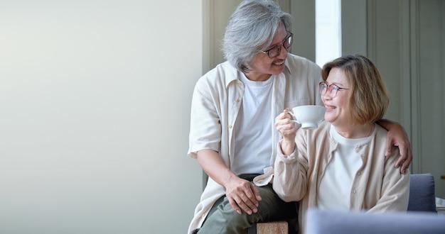 Família feliz, casal sênior abraçando e provocando enquanto bebe um café. Foto Premium