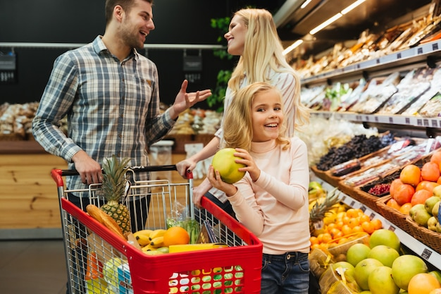 Família feliz com carrinho de compras Foto gratuita