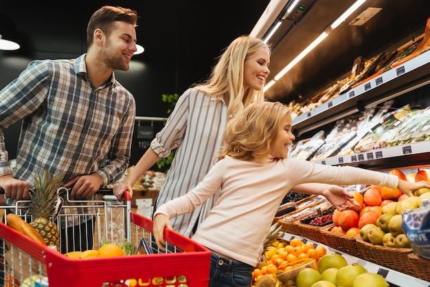 Família feliz com criança e carrinho de compras, comprando comida Foto gratuita
