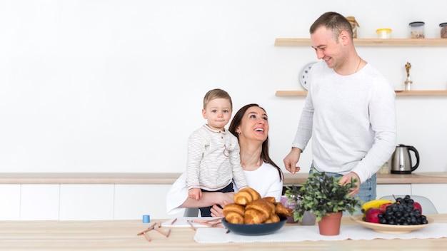 Família feliz com criança na cozinha e copie o espaço Foto gratuita