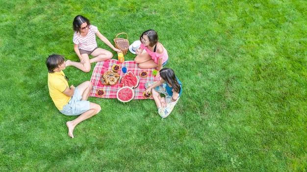 Família feliz com crianças fazendo piquenique no parque, pais com filhos sentados na grama do jardim e comer refeições saudáveis ao ar livre Foto Premium