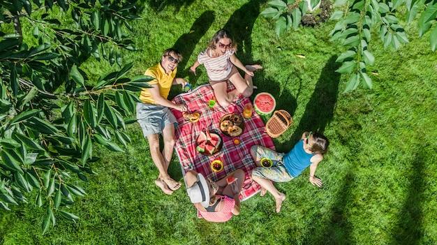 Família feliz com crianças fazendo piquenique no parque Foto Premium
