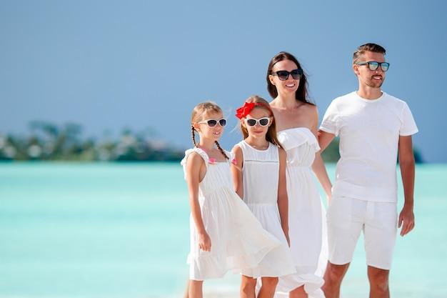 Família feliz com crianças na praia junto Foto Premium
