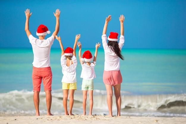 Família feliz, com dois filhos no chapéu de papai noel nas férias de verão Foto Premium