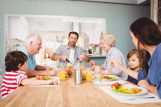 Família feliz com os avós, sentado à mesa de jantar Foto Premium