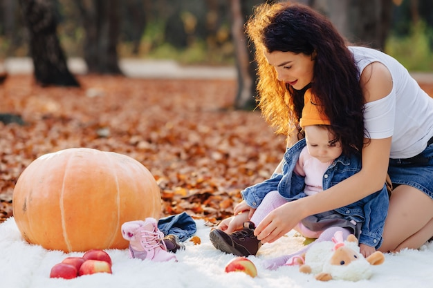 Família feliz, com, pequeno, cute, criança, parque, ligado, folha amarela, com, grande, abóbora, em, outono Foto Premium