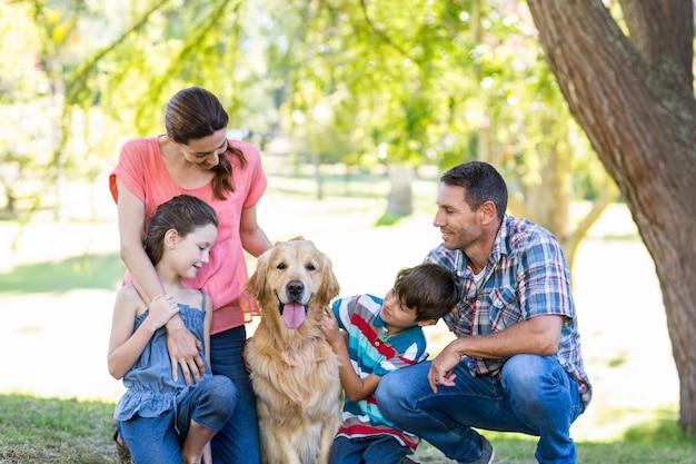 Família feliz com seu cachorro no parque Foto Premium