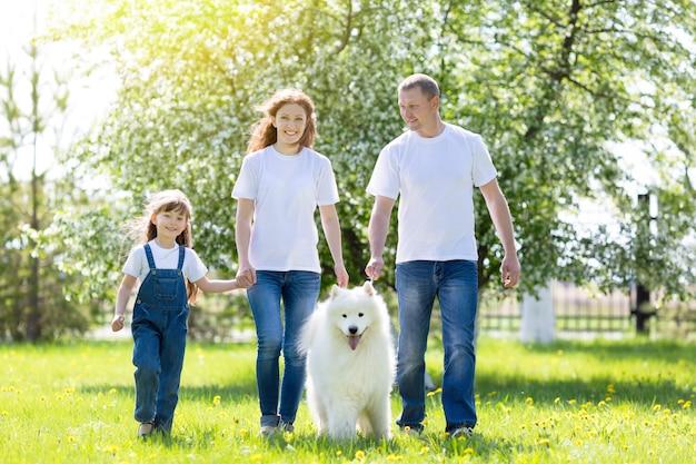 Família feliz com um cachorro branco em um parque de verão. Foto Premium