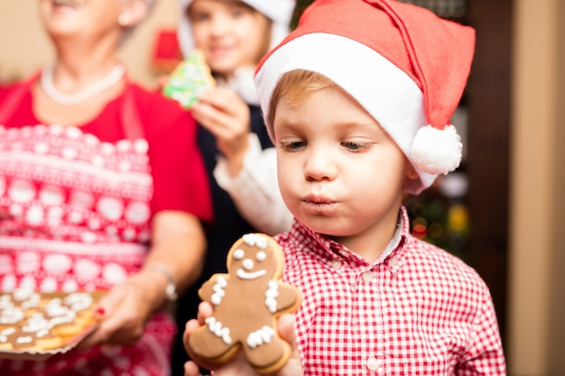 Família feliz com uma bandeja de biscoitos no Natal Foto gratuita
