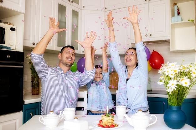 Família feliz comemora aniversário em casa na cozinha Foto Premium