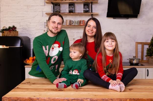 Família feliz comemorando o natal na cozinha Foto Premium