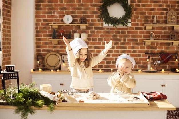 Família feliz crianças engraçadas estão preparando a massa, jogando com farinha na cozinha Foto Premium
