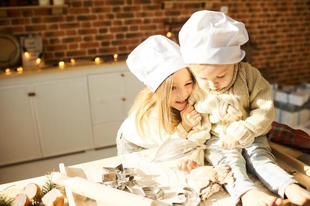 Família feliz crianças engraçadas estão preparando a massa Foto Premium