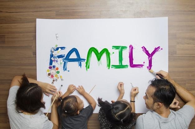 Família feliz da vista superior que encontra-se no assoalho com pintura usando aquarelas Foto Premium