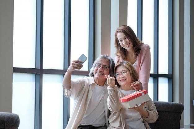 Família feliz dar presentes um ao outro em ocasiões importantes e fotografado. Foto Premium