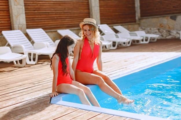 Família feliz de férias. mãe e filha em trajes de banho e óculos de sol, sentadas à beira da piscina. Foto gratuita