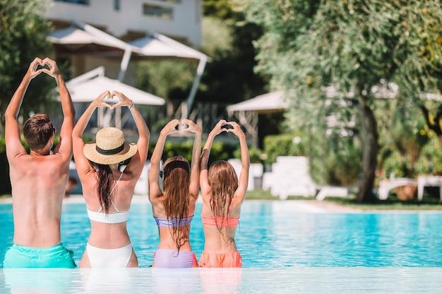 Família feliz, de, quatro, em, ao ar livre, piscina Foto Premium