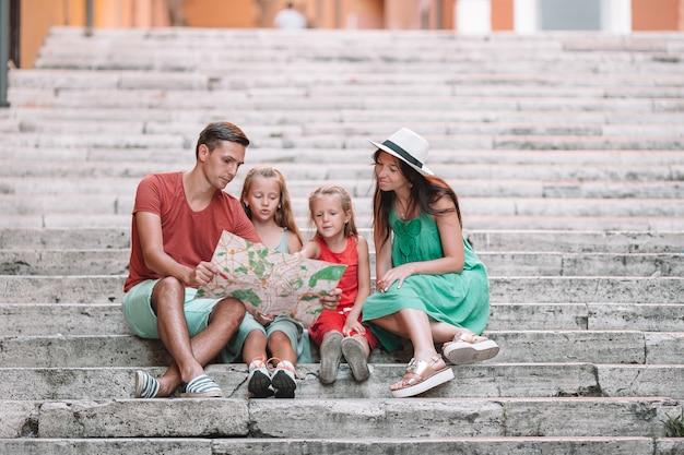 Família feliz de quatro pessoas em roma com mapa Foto Premium