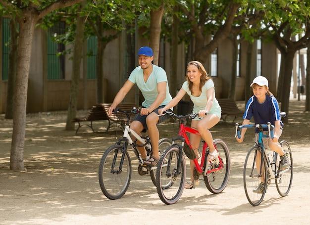 Família feliz de três ciclismo na rua Foto gratuita
