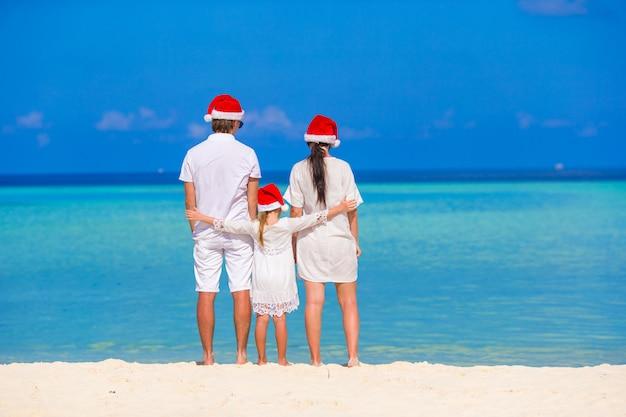 Família feliz de três em chapéus de papai noel durante as férias tropicais Foto Premium