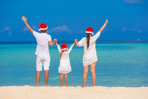 Família feliz de três em chapéus de papai noel na praia Foto Premium