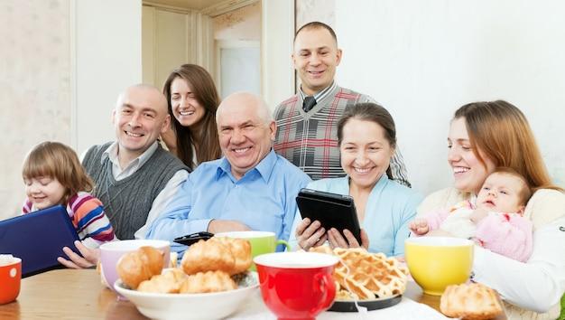 Família feliz de três gerações com dispositivos eletrônicos Foto gratuita
