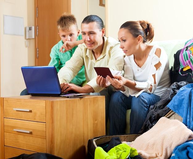 Família feliz de três hotéis reservando na internet usando laptop Foto gratuita