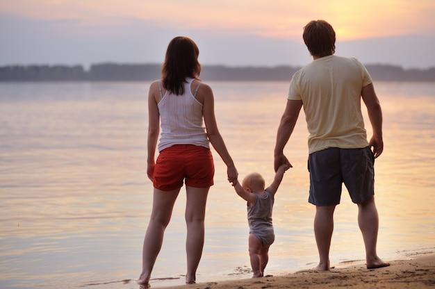 Família feliz de três na praia ao pôr do sol Foto Premium