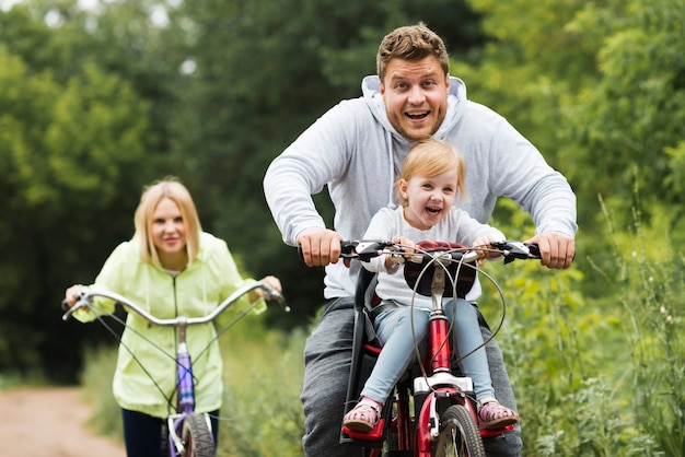 Família feliz de vista frontal com bicicletas Foto gratuita
