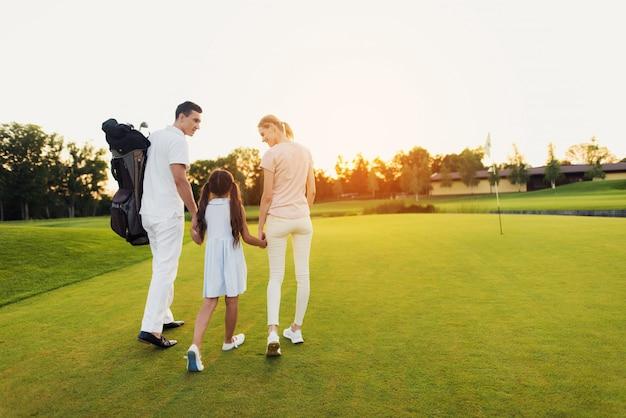 Família feliz deixa o campo de golfe após o jogo. Foto Premium