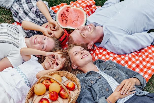 Família feliz, descansando no piquenique. apreciando e deitado no xadrez xadrez no prado. adultos e crianças olham para o céu Foto Premium