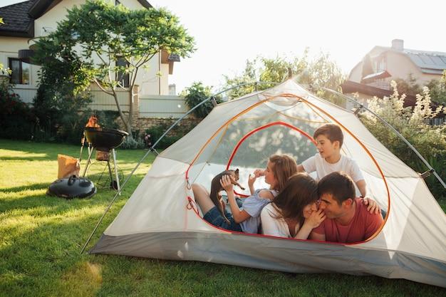 Família feliz desfrutando na tenda de cam no parque Foto gratuita