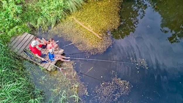 Família feliz e amigos pescando juntos ao ar livre perto do lago no verão, vista superior aérea de cima Foto Premium