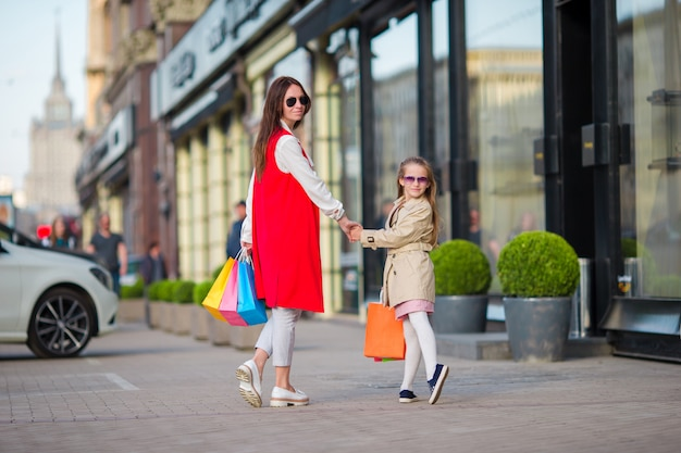 Família feliz em fazer compras ao ar livre. mãe e filha fazem compras nas compras e se divertem andando na rua ao ar livre. Foto Premium