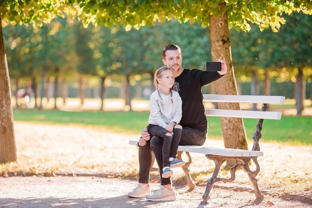 Família feliz em queda. pai e filho se divertir tomando selfie no lindo dia de outono Foto Premium