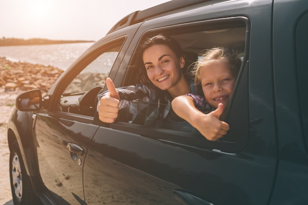 Família feliz em uma viagem em seu carro. pai, mãe e filha estão viajando pelo mar ou pelo oceano ou pelo rio. passeio de verão de automóvel Foto Premium
