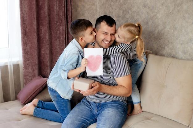 Família feliz, filha e filho dão um presente e um cartão para o pai para o feriado. Foto Premium